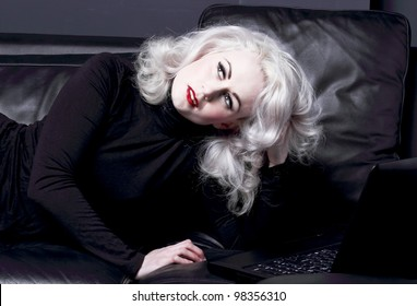 Woman thinking, lying on black leather sofa with laptop in front of her