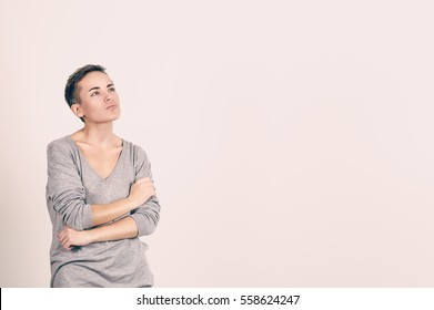 Woman thinking. Portrait close up of happy beautiful young woman thinking looking away, up isolated grey wall background with copy space. Human face expressions, emotions feelings, body language