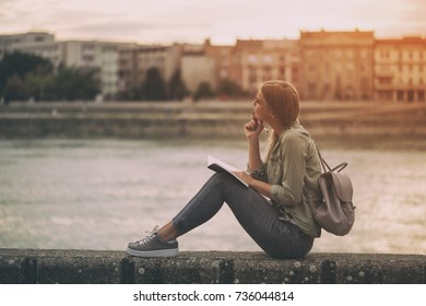 Woman thinking and writing at her notebook while sitting at the riverbank.Woman writing Image is intentionally toned.