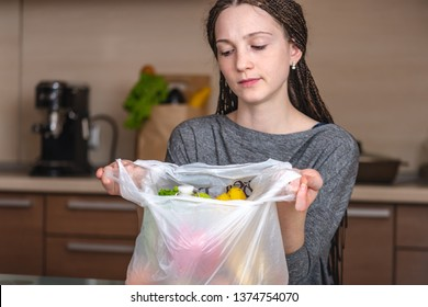 A woman thinks that would refuse to use a plastic bag to buy products in the store. The concept of environmental protection and the abandonment of plastic