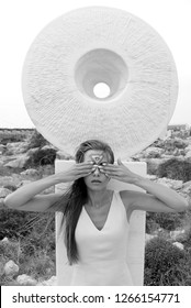 Woman with a third eye painted on her forehead. Covered her eyes with her hands. Black and white photo.