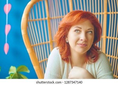 Woman with a thoughtful dreaming look sits in a cafe on a beautiful chair on Valentine's day with a decor behind her in the form of hearts