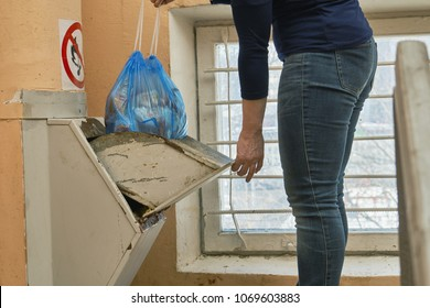 Woman throwing away a garbage packed in a garbage bag using a home garbage chute in Moscow (Russia )