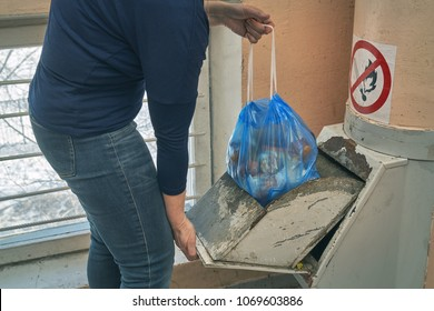 Woman throwing away a garbage packed in a garbage bag using a home garbage chute in Moscow dwelling house