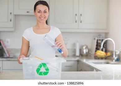 Woman throwing bottle into recycling bin in kitchen
