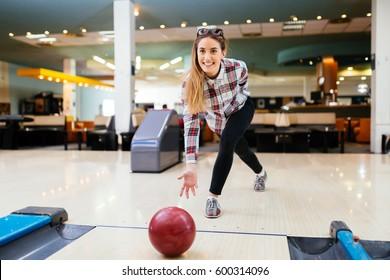 Woman throwing bowling ball in club