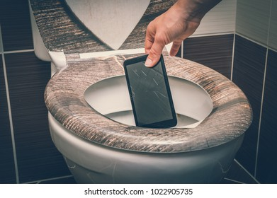 Woman throwing broken mobile phone in the toilet bowl - retro style