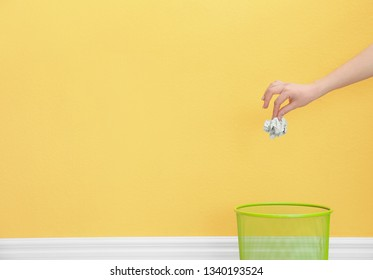 Woman throwing crumpled paper into metal bin against color background. Space for text