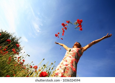 woman throwing flowers in the air in a field of poppies
