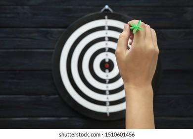Woman throwing green arrow at dart board on dark wooden background, closeup