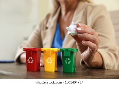 Woman throwing paper into mini recycling bin at office, closeup