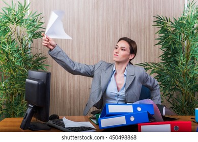 Woman throwing papers in the office under stress