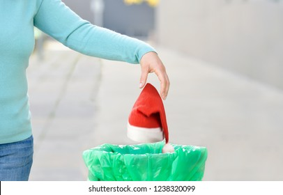 Woman throwing a santa hat to the trash in a trash bin a city after Christmas