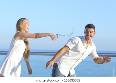 Woman throwing water to her boyfriend with the sky in the background