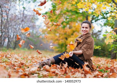 woman throws autumn leaves in the park