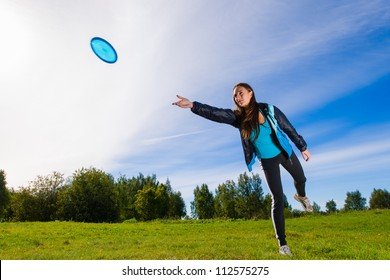 Woman throws a blue disc on the lawn