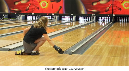 A woman throws a bowling ball on the track in order to knock down the pins.