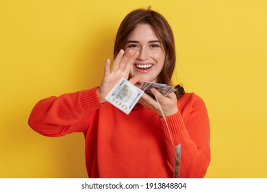 Woman throws up cash, lottery winner with very happy expression, looking directly at camera and smiling, lady with banknotes indoor, dark haired girl with her currency, has reward.