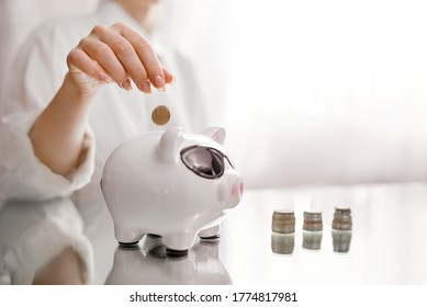 Woman throws coins in pig piggy bank from stacks