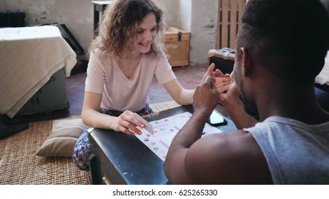 Woman throws dice and takes card. Man takes her hand and draws a finger. Multiethnic couple plays the boar game.