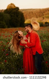Woman throws up her hay hat standing with her man on a green field