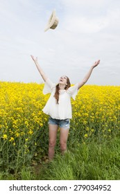 A woman throws her straw hat in the air standing in the middle of a yellow field
