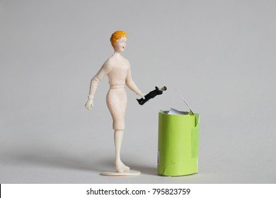 Woman throws tiny man in a trash can.  Concept of ending bad relationships or ditching a bad boss. Breakup or divorce. Concept of employment or romantic rejection. Frustration with online dating.