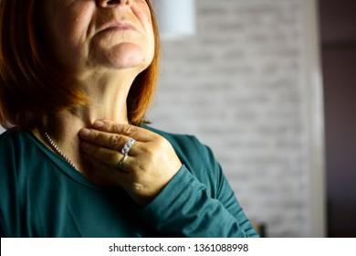 Woman thyroid gland control. Senior lady sweeping the laryngeal, laryngitis, goiter or Hypothyroidism. Disorder of the endocrine system. Hashimoto's Thyroiditis, Lymphocytic Thyroiditis.