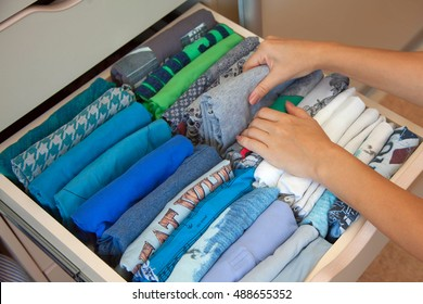 The woman is tidying up the male wardrobe. Drawer with men's shirts. The order in the closet.