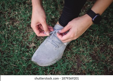 A woman tie shoelaces on grass field.A sportsgirl tying shoelaces on sneakers close up. A wowan athlete tying shoelaces on sneakers outdoors
