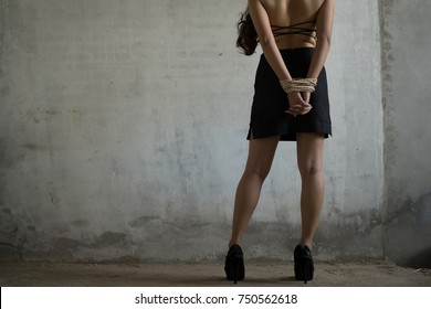 Woman tied with rope sexual robber concept, bandit sexual abuse or femae hostage in abandoned house