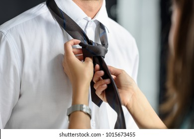 Woman ties a knot on male tie