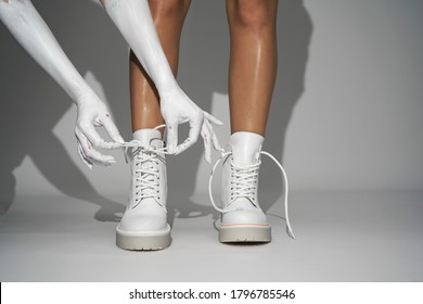 woman ties the laces on white shoes on a light background in the studio. close-up fashion footwear new collection autumn winter 21/22 fashion shooting