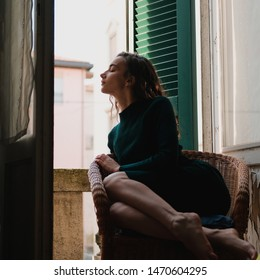 Woman in tight knit dress sitting in wicker chair on a balcony with green wooden shutters in traditional italian hotel. Female solo travel concept.