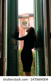 Woman in tight knit dress stands on a balcony with green wooden shutters in traditional italian hotel. Female solo travel concept.