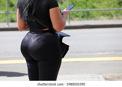 Woman in tight pants stands by the road with smartphone in her hand