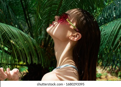 Woman tilted her head back and trendy glasses nature island
