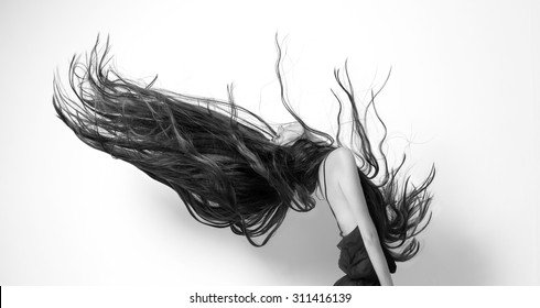 woman tilted her head back and her long hair scattered in the shape of the wing. shot in studio