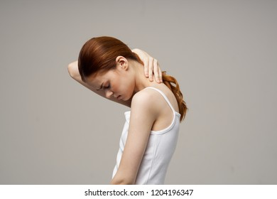 woman tilts her head and holds her neck