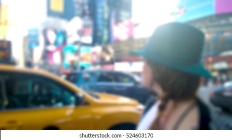woman in Time Squared New York with a yellow cap taxi. blurred background
