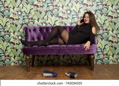 Woman tired after party is talking on the phone on the purple sofa