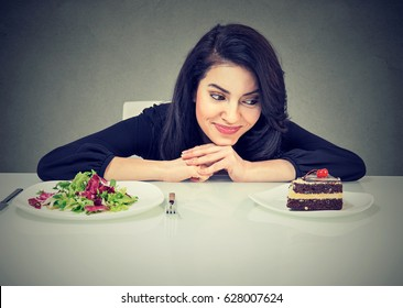 Woman tired of diet restrictions deciding whether to eat healthy food or sweet cake she is craving
