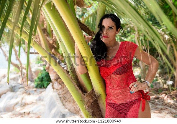 the woman was tired of the tour, stopped to relax in the shade under a palm tree on the beach