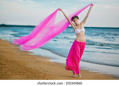 Woman with a tissue in his hands on the beach near the water