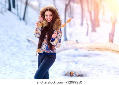 woman toasting sausages on grile in winter. woman in winter jacket near the fire