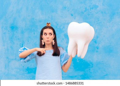 Woman in Tooth Fairy Costume Holding Big Molar. Funny princess holding an oversized fallen baby tooth