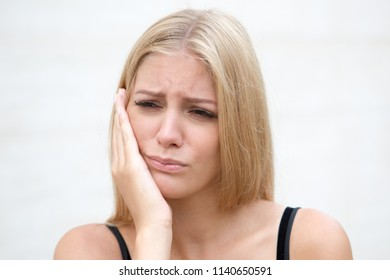Woman with toothache outside