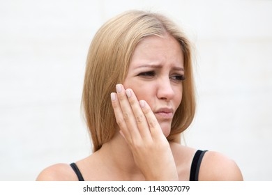 Woman with toothache outside in summer