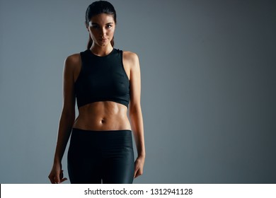 woman with a torso-built Fitness dark clothes gray isolated background
