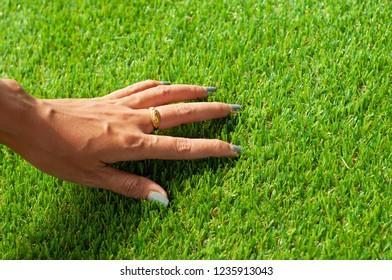 Woman touch soft artificial grass. Green Artificial turf surface